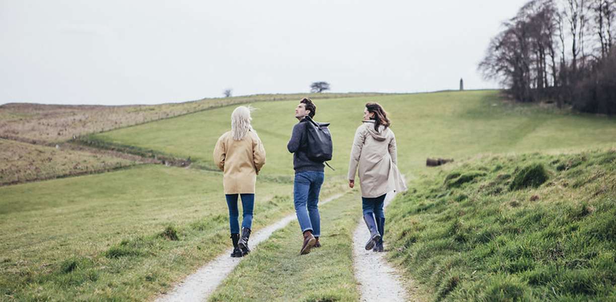 Three friends walking up a path on a Wiltshire hillside